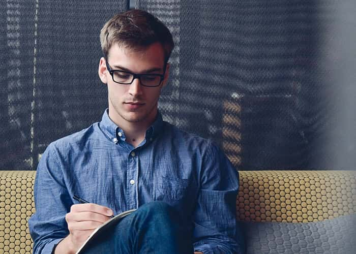 Man in a blue shirt writing on a notebook