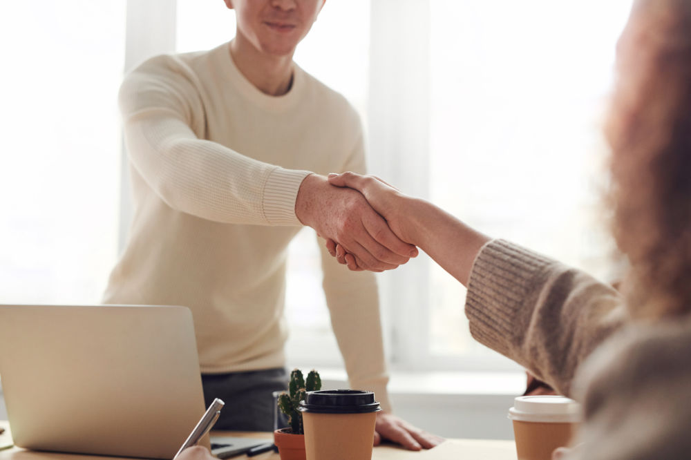 Businessman in a white sweater shaking hands with a client