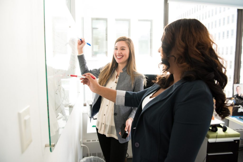 two women smiling learning profit management